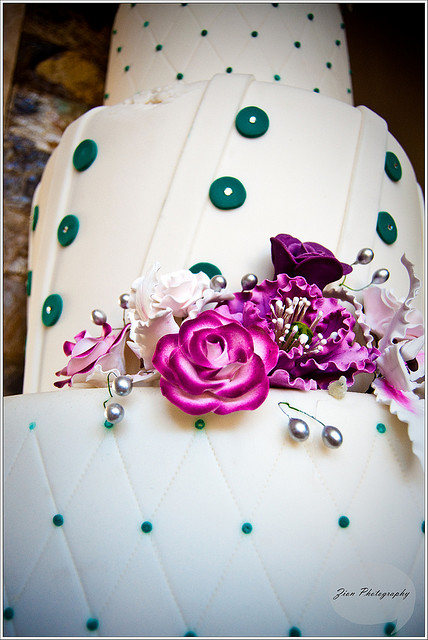 White cake teal and purple flower wedding cake